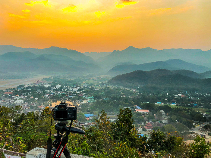 A canon DSLR set up on a tripod in front of a stunning mountainous landscape - how to sell landscape photos
